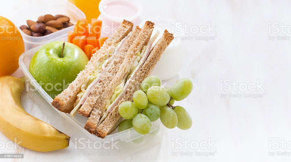 school lunch with sandwiches and fruit on white background stock photo