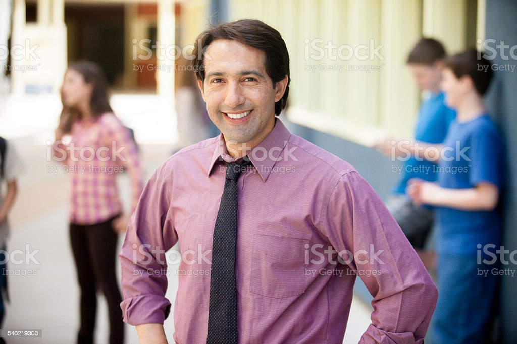 School Principal Smiling in front of students on campus stock photo