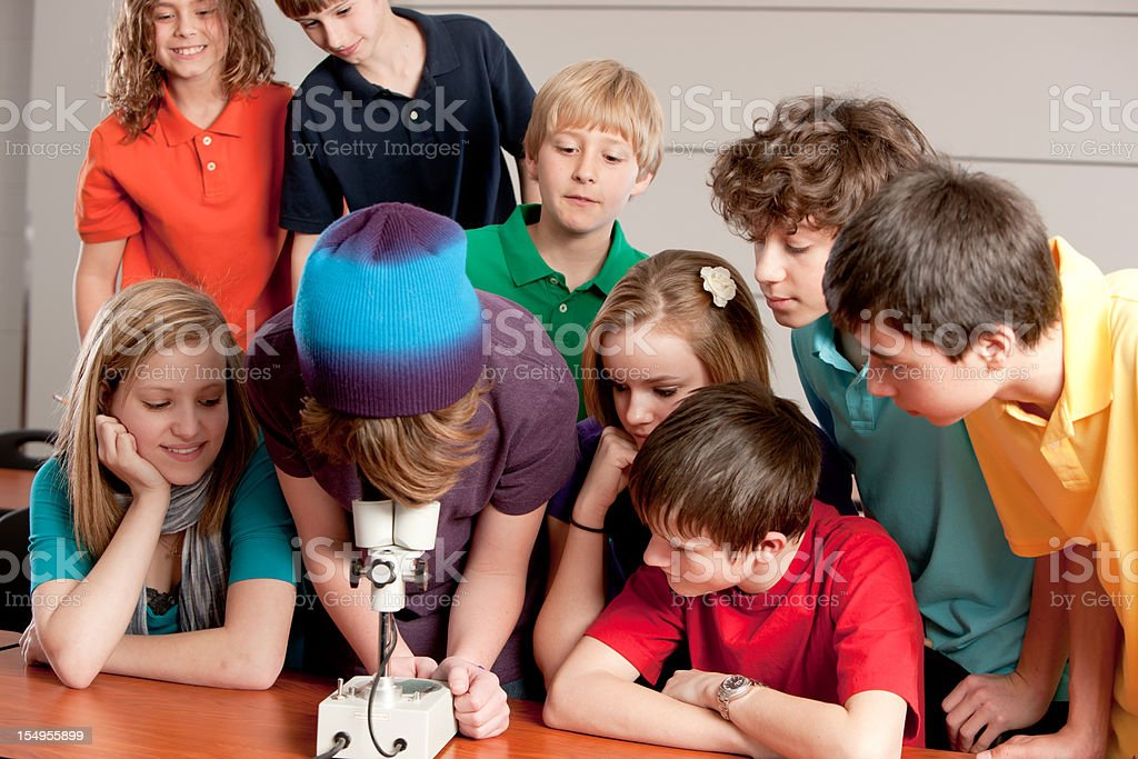 School Science: Students Study Using Microscope in the Classroom royalty-free stock photo