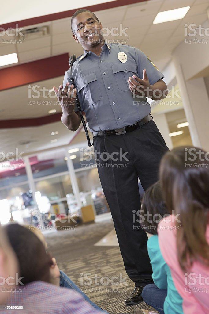 School security or police officer teaching safety procedures to students royalty-free stock photo