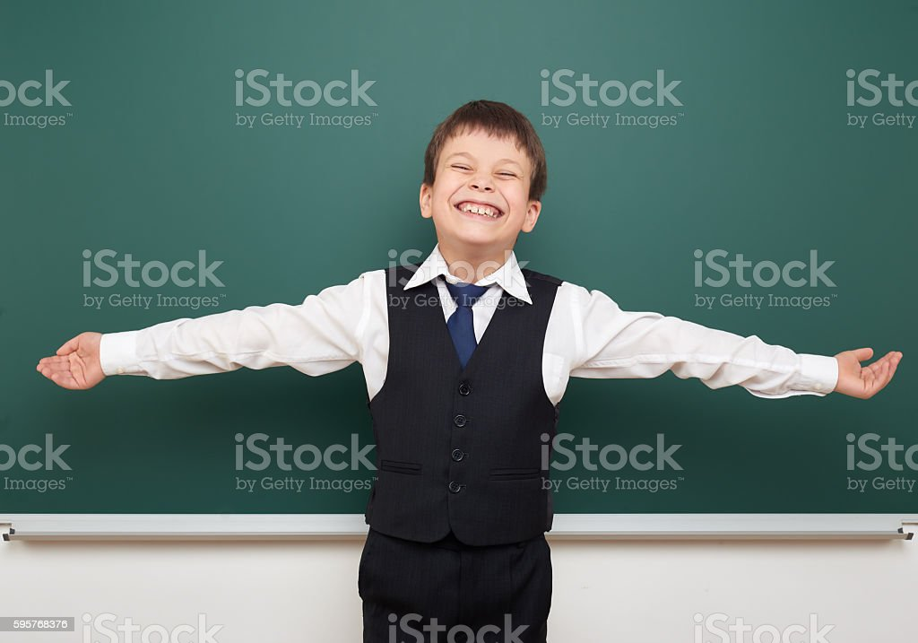 school student boy posing at the clean blackboard, education concept stock photo