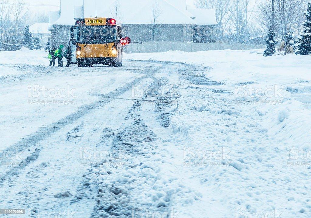 School Students Boarding Blizzard Snow Storm School Bus stock photo