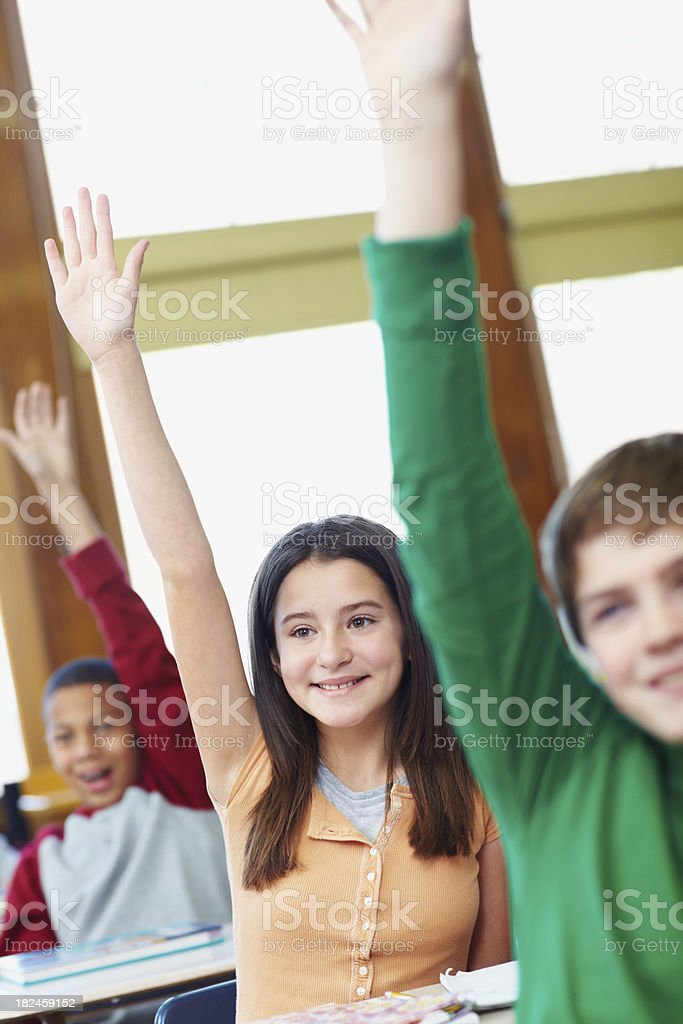 School students raising hands in classroom royalty-free stock photo