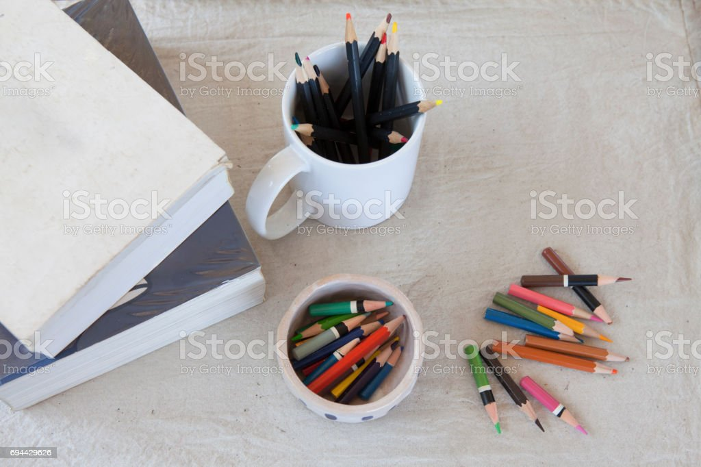 School supplies concept on mulberry paper background , Books ,crayons in  porcelain cup and coloring pencils ready for your design. stock photo