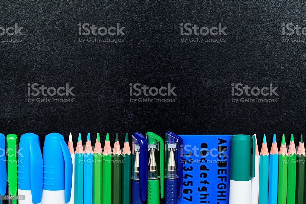 School supplies covering bottom of blackboard stock photo