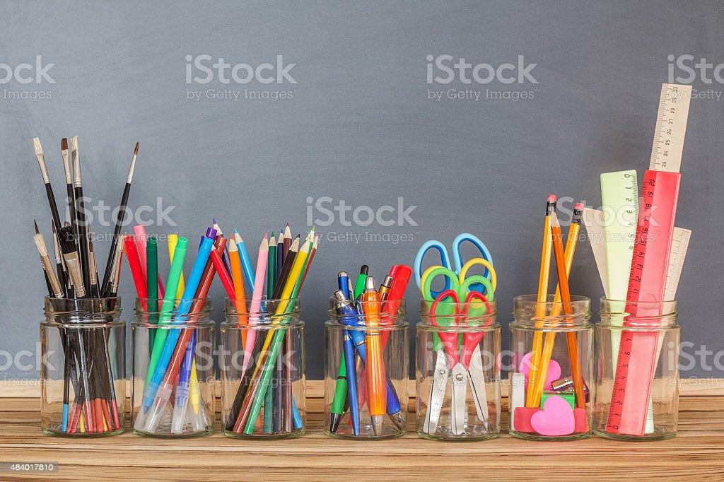 School supplies in jars stock photo
