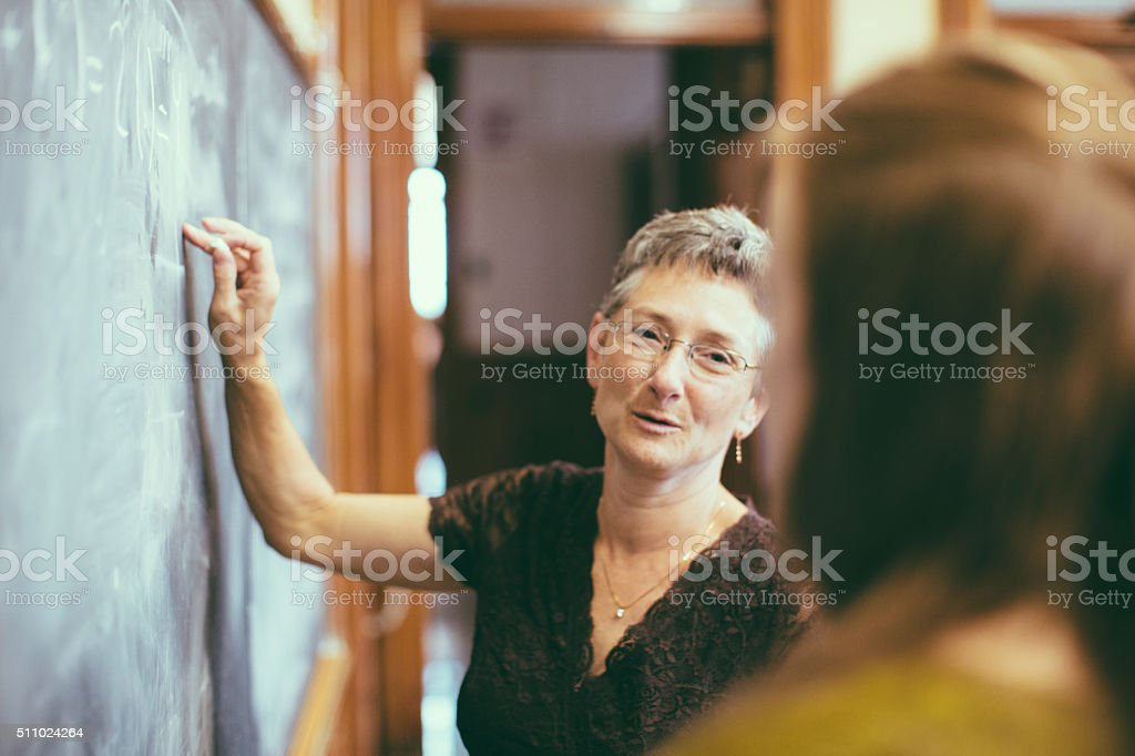 School teacher at chalkboard explaining math teenage student stock photo