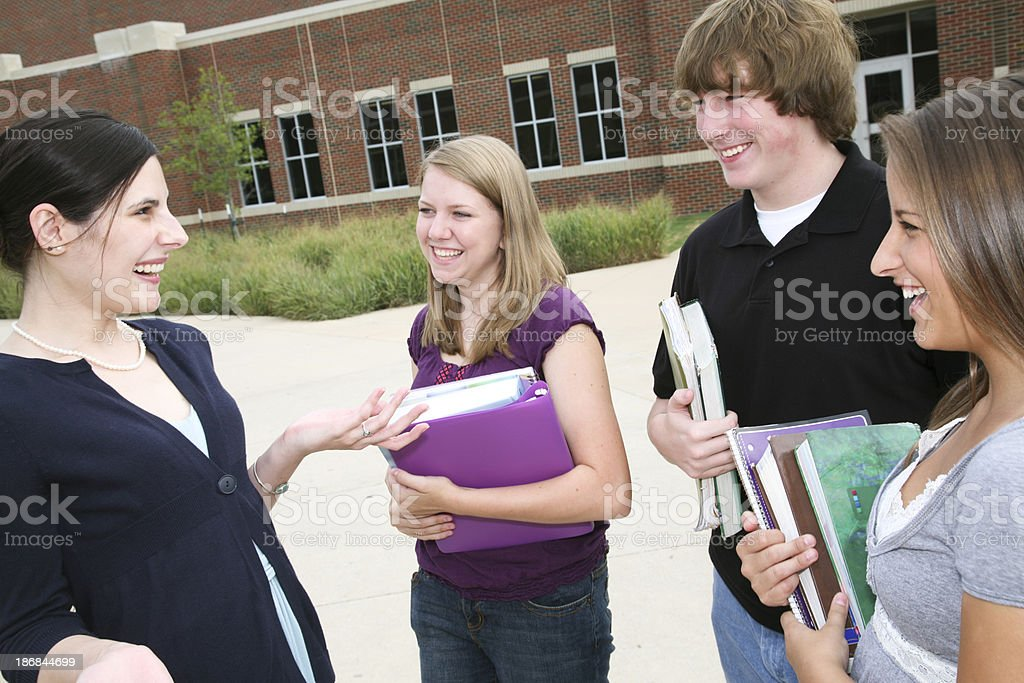 School Teacher Lifting Hands While Talking to Her Students royalty-free stock photo