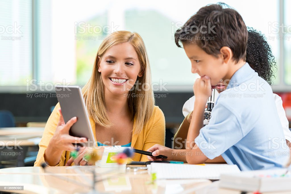 STEM school teacher uses digital tablet to help student stock photo