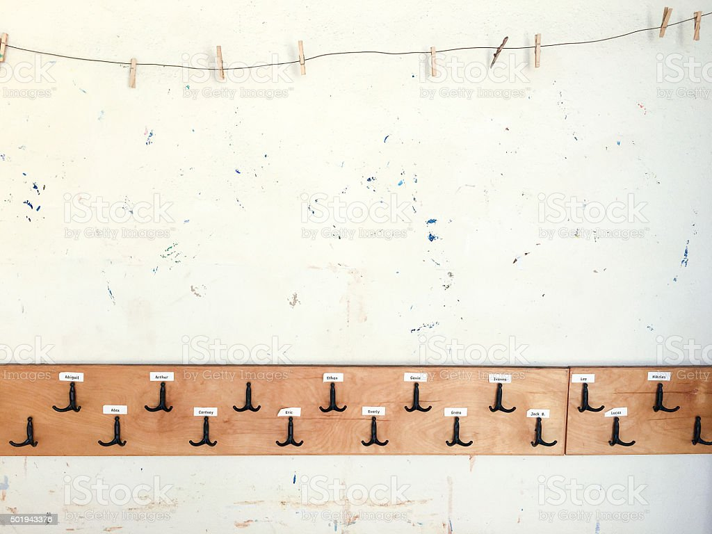 School wall with empty clothespins and backbpack hooks stock photo