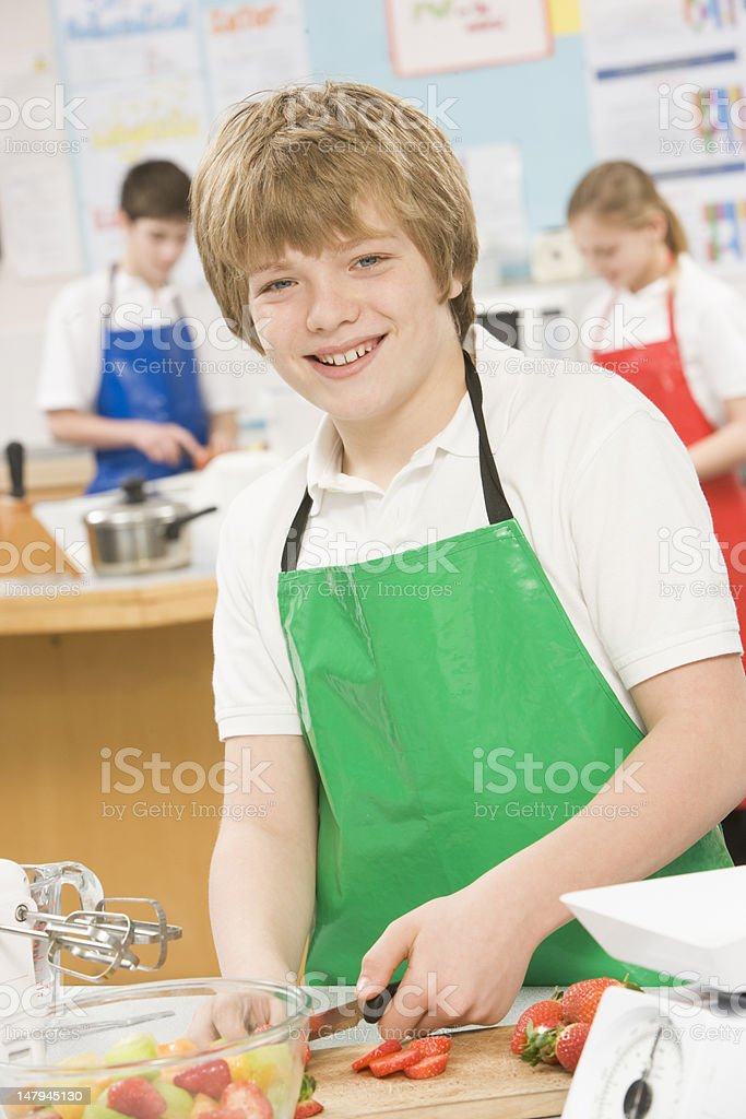 Schoolboy at school in a cooking class royalty-free stock photo