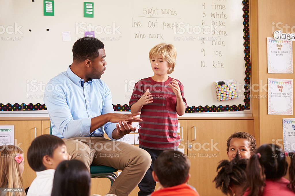 Schoolboy at the front of elementary class with teacher stock photo