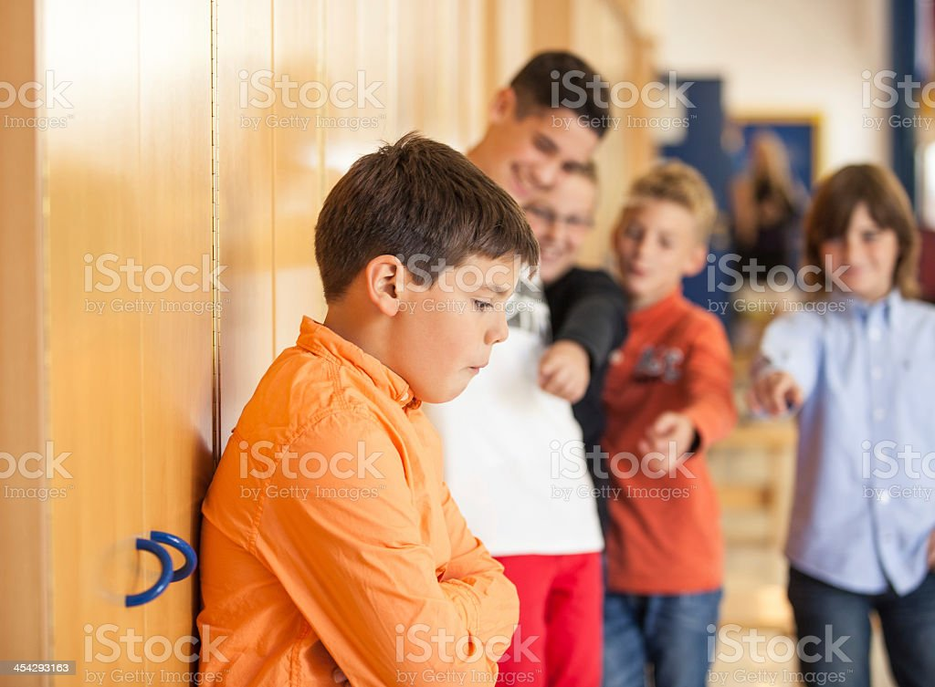 A schoolboy being bullied at school by his friends stock photo