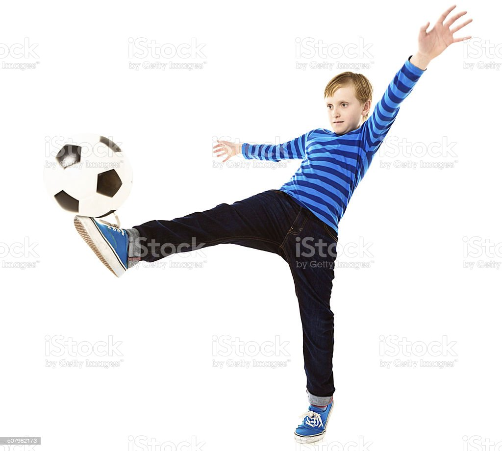 Schoolboy bends over backwards for balance while kicking football stock photo