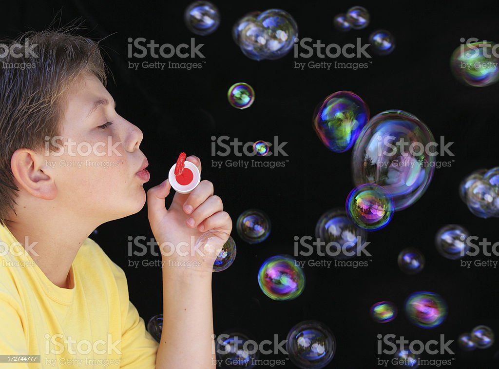 Schoolboy blowing bubbles royalty-free stock photo