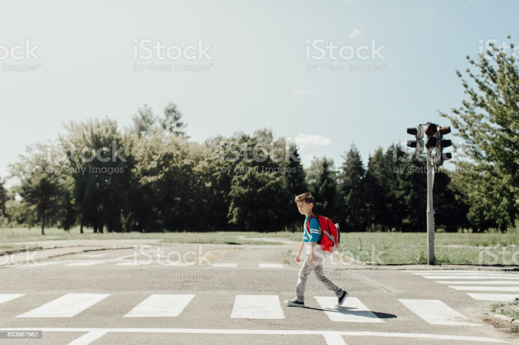 Schoolboy crossing a road on his morning way to school stock photo