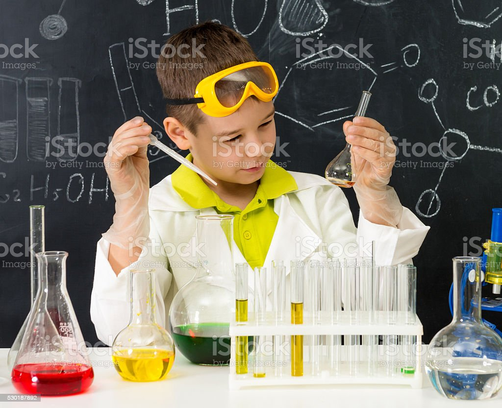 schoolboy gown and gloves watching chemical experiment in tube stock photo