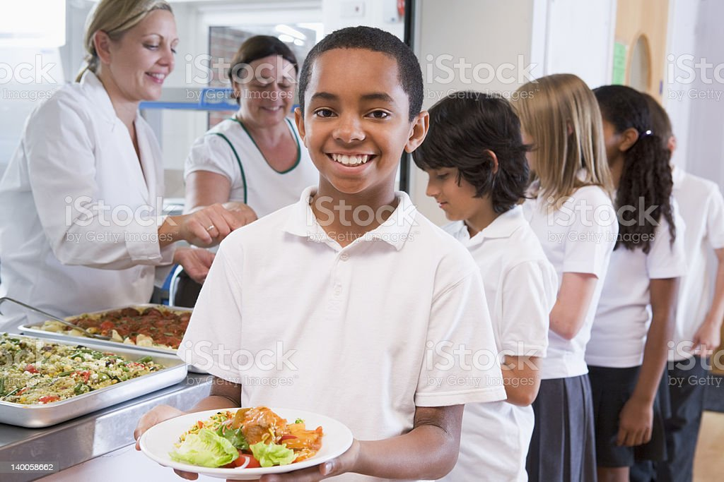 Schoolboy holding plate of lunch in school cafeteria stock photo