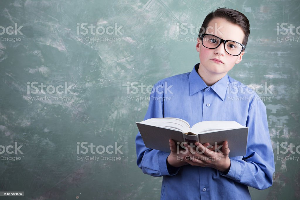 schoolboy in glasses reading book stock photo