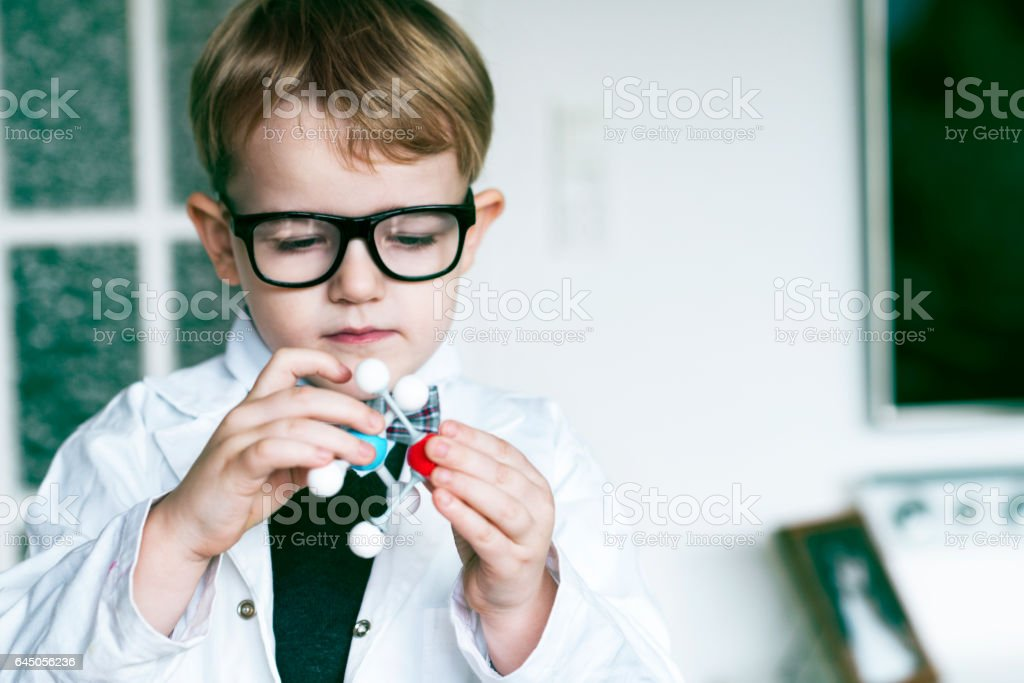 Schoolboy makes scienticfic experiment with molecular structure stock photo