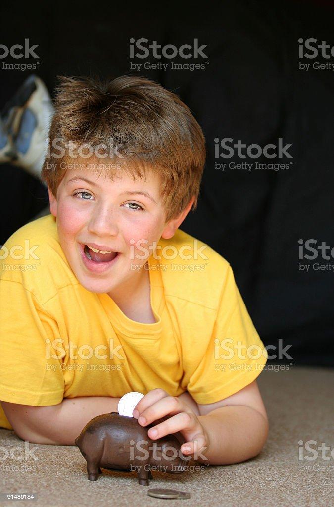 Schoolboy putting coin into a piggy bank stock photo