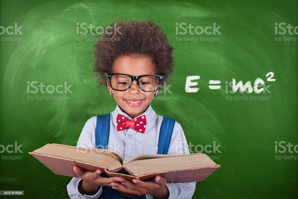 Schoolboy reading a book in front of school board stock photo