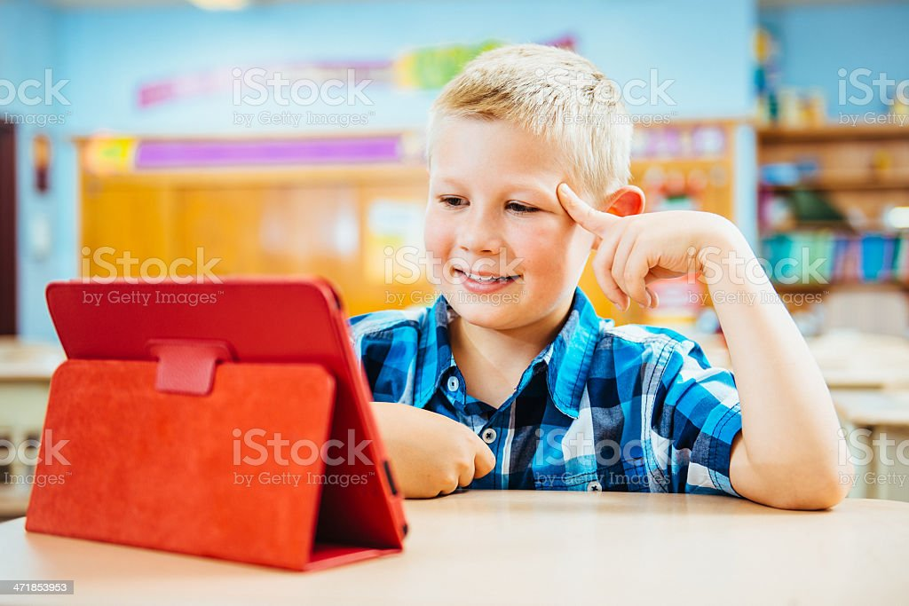 Schoolboy reading from digital tablet royalty-free stock photo