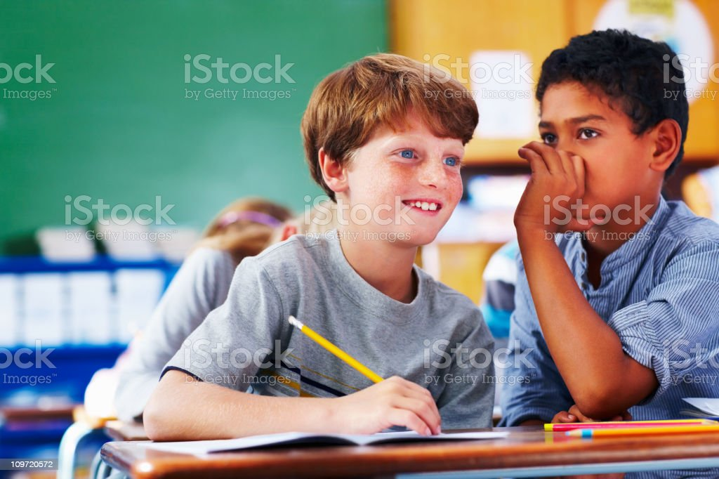 Schoolboy sharing a secret with his friend royalty-free stock photo