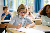 schoolboy sits in classroom, writes in his notes