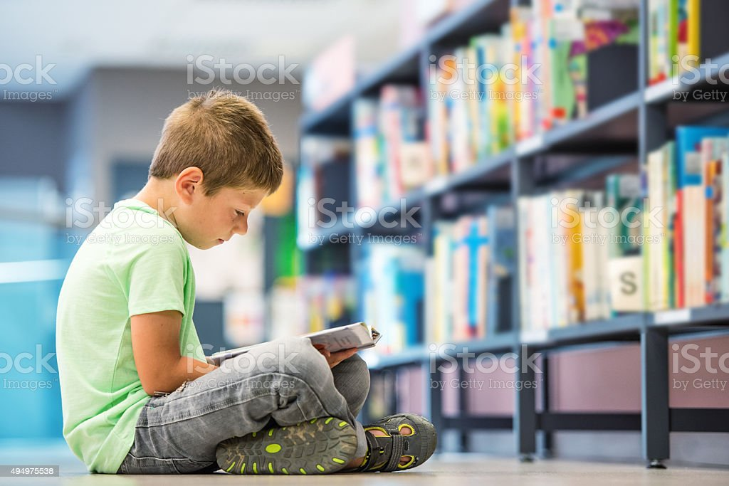 Schoolboy sitting on the floor in library stock photo