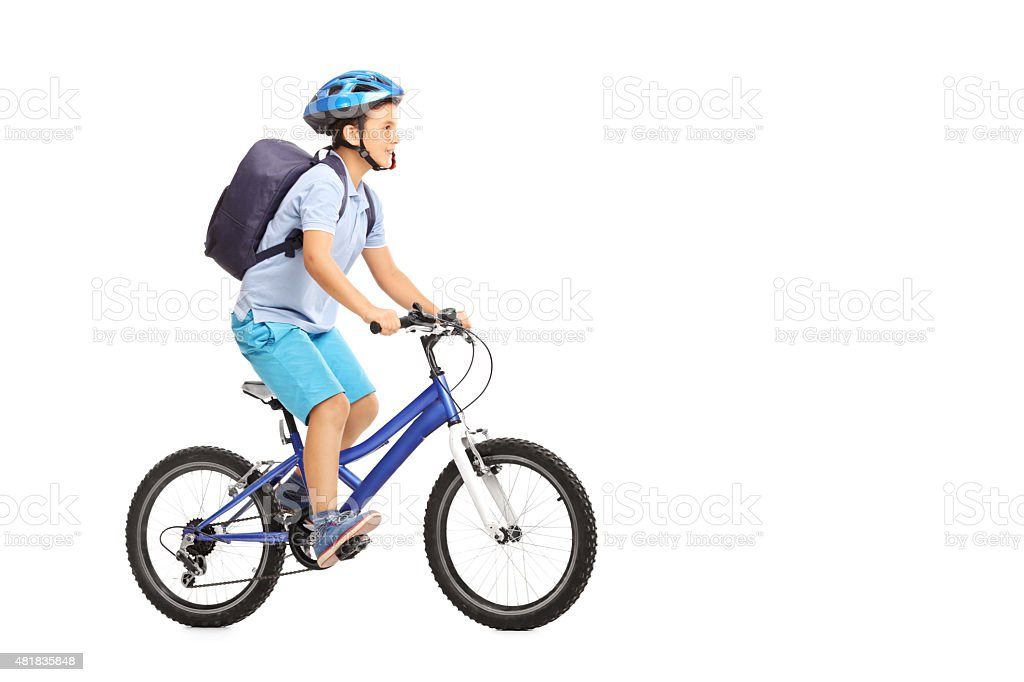 Schoolboy with a helmet riding a bike stock photo