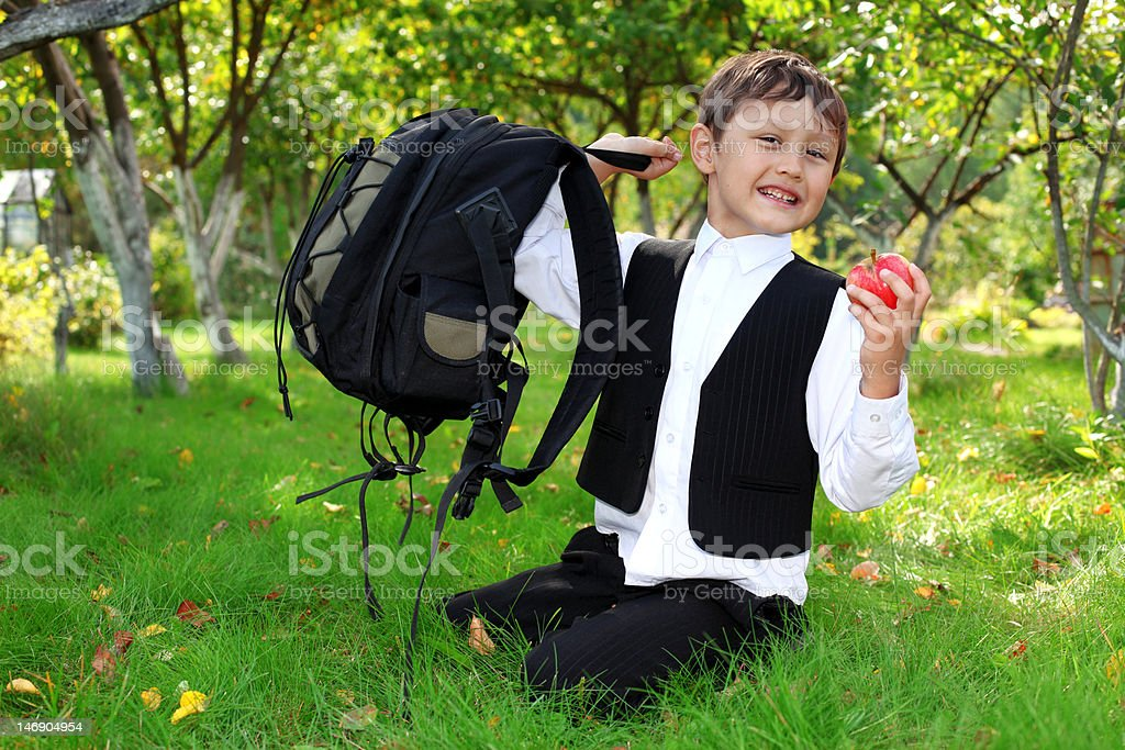 schoolboy with backpack and apple royalty-free stock photo