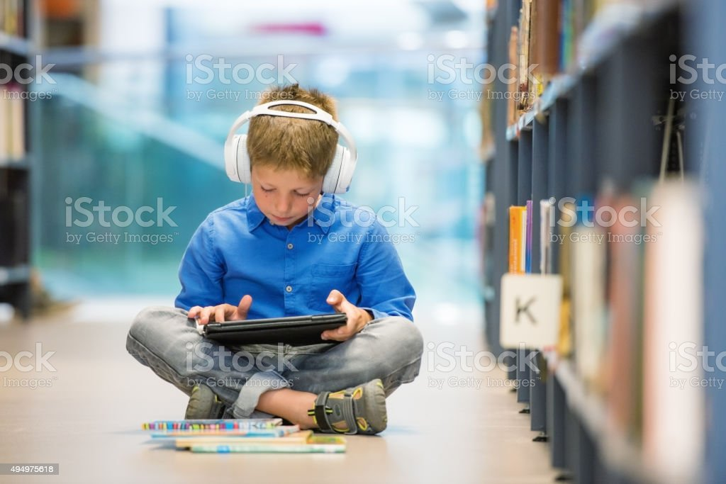 Schoolboy with headphones and digital tablet sitting on library floor stock photo