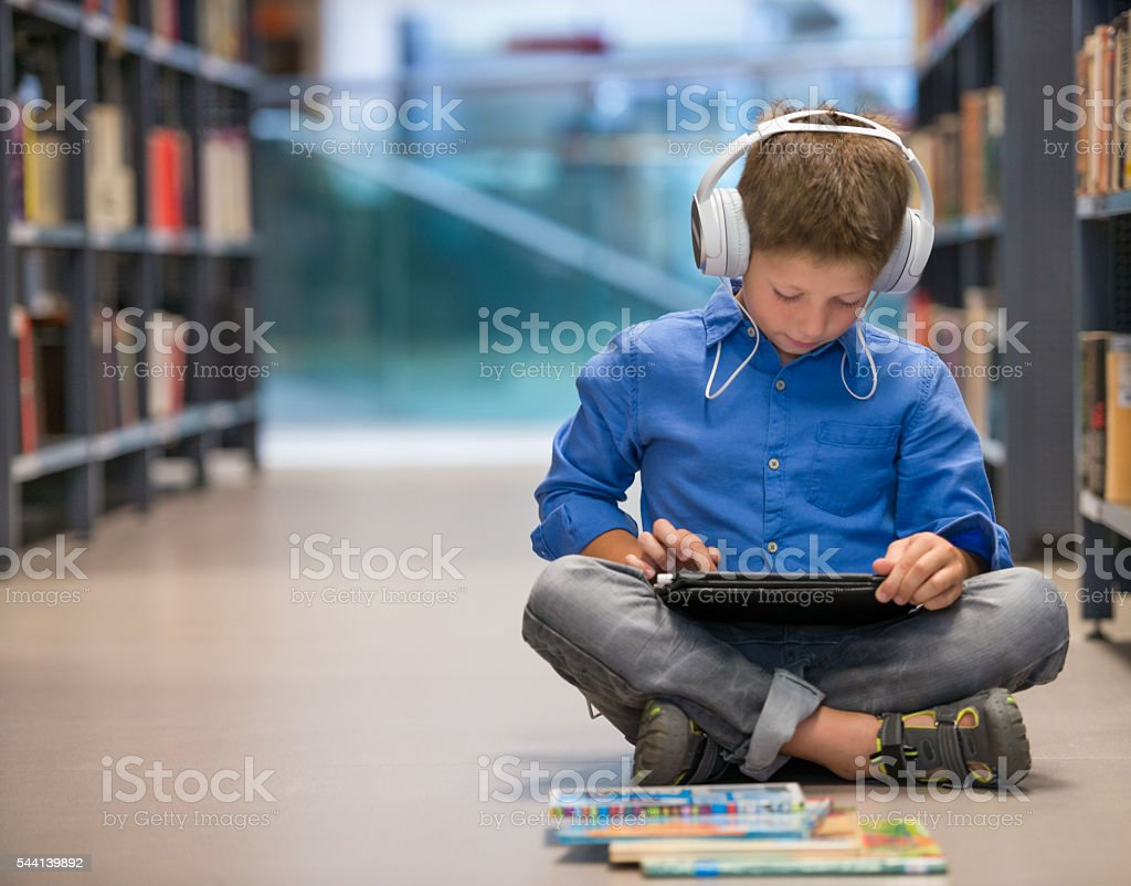 Schoolboy With Headphones And Tablet Computer In Library stock photo