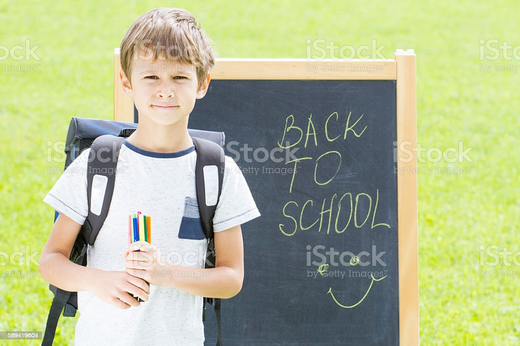 Schoolboy with pens and backpack against the blackboard. Education, Back stock photo