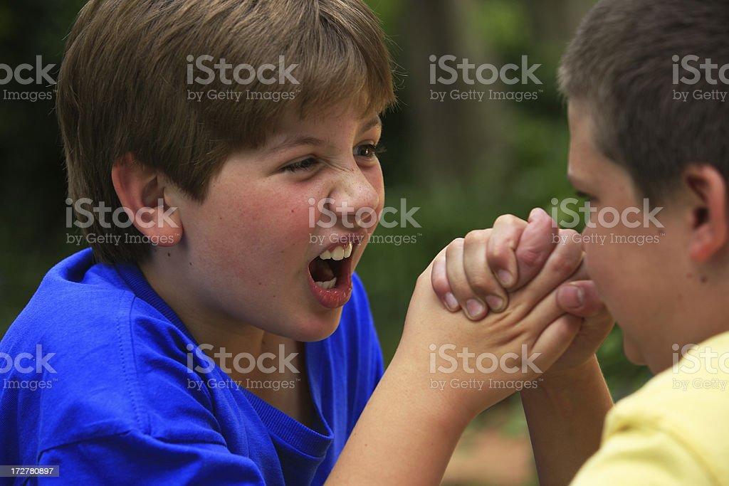 Schoolboys arm wrestling stock photo