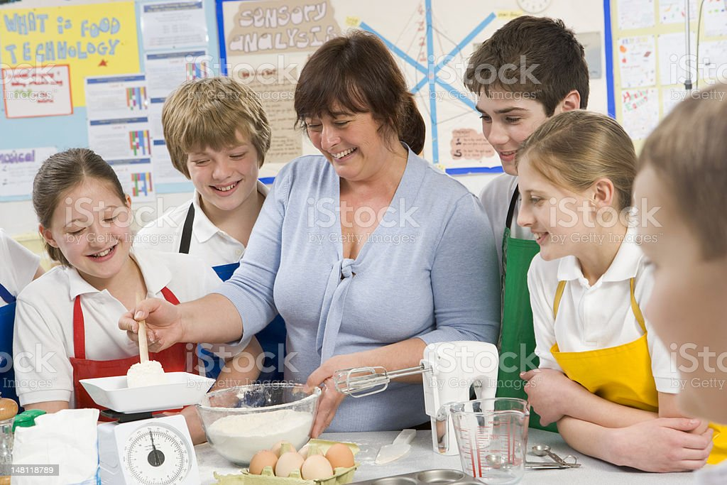 Schoolchildren and teacher at school in a cooking class stock photo