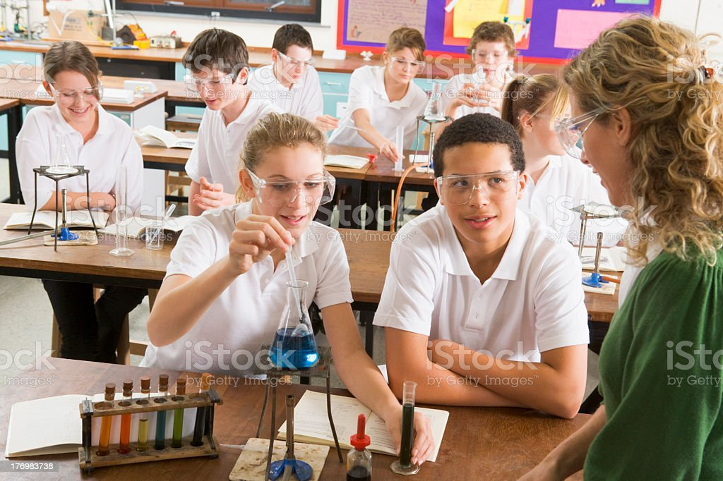 Schoolchildren and teacher conducting a science experiment stock photo