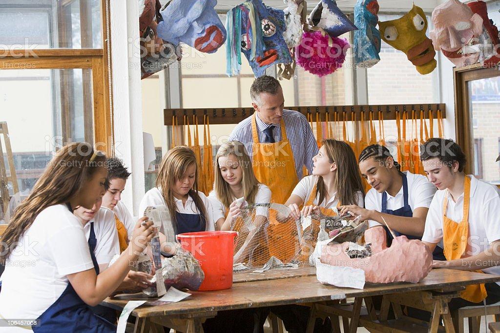 Schoolchildren and teacher sitting around a table in art class stock photo