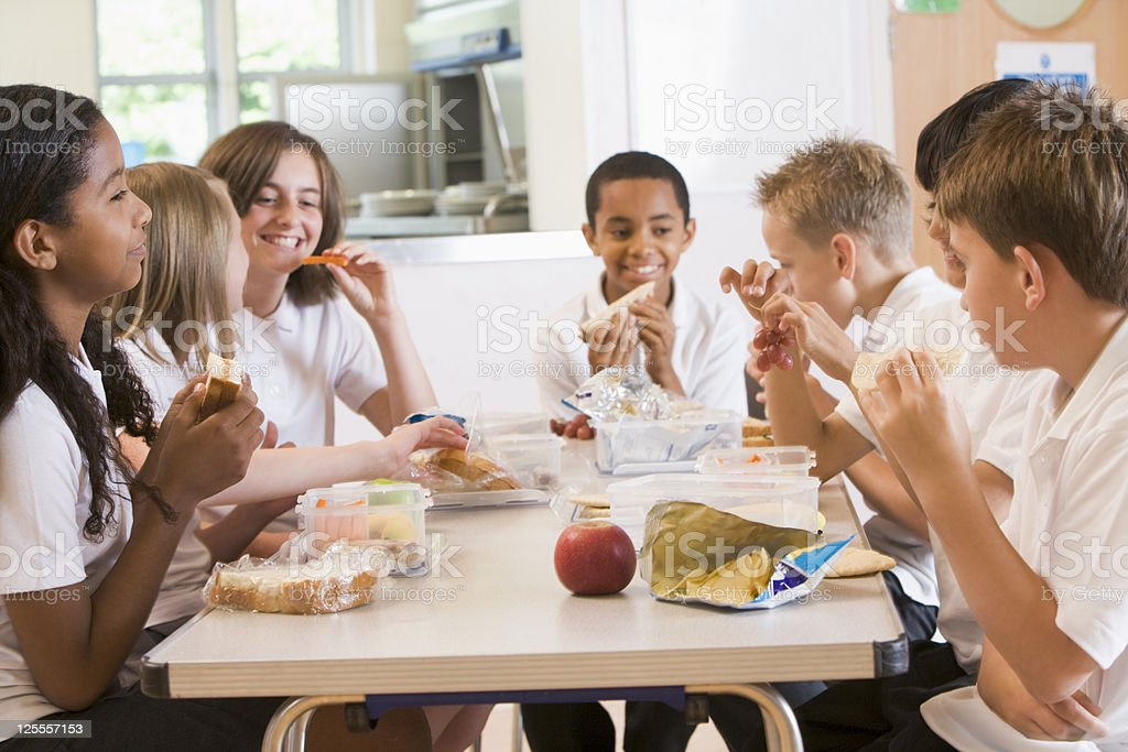 Schoolchildren enjoying their lunch in a school cafeteria stock photo