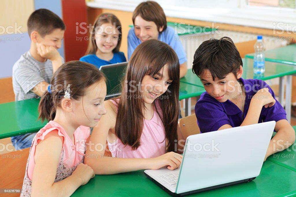 Schoolchildren having fun on laptops at  classroom. royalty-free stock photo
