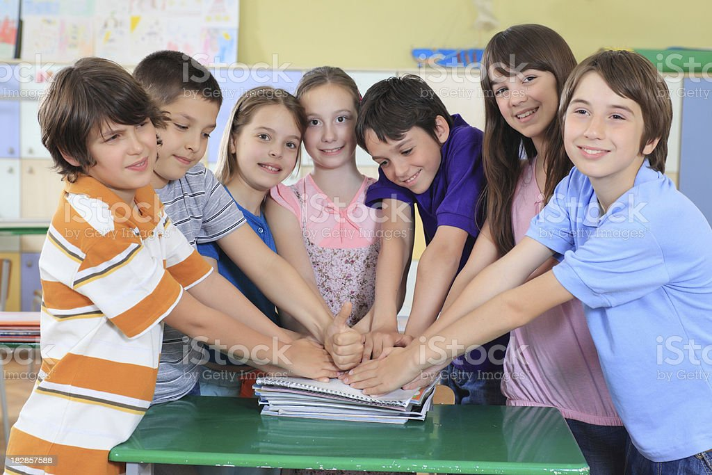 Schoolchildren holding hands on top of each other. royalty-free stock photo