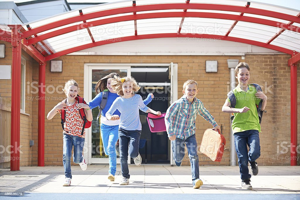 Schoolchildren Running Into Playground At End Of Class stock photo