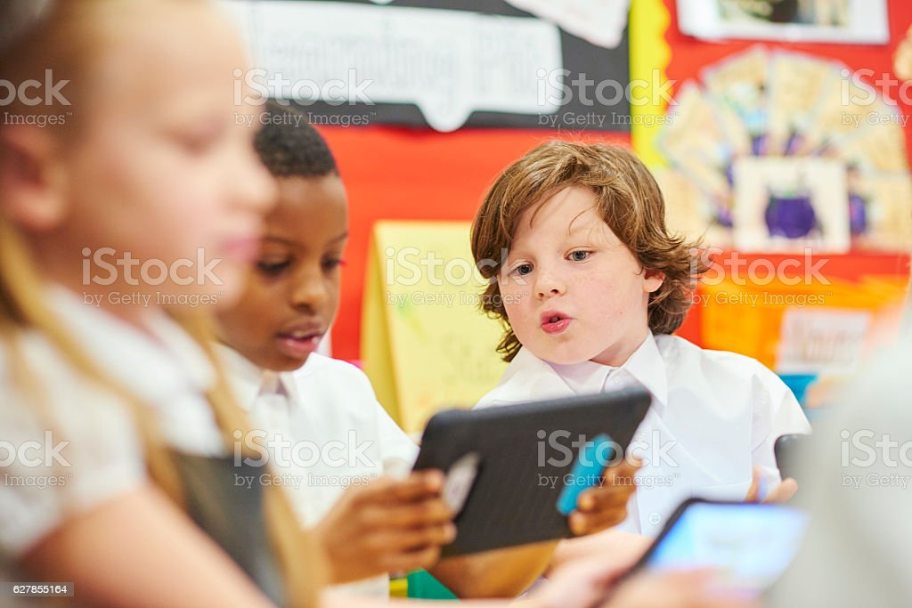 schoolchildren with tablets learning stock photo