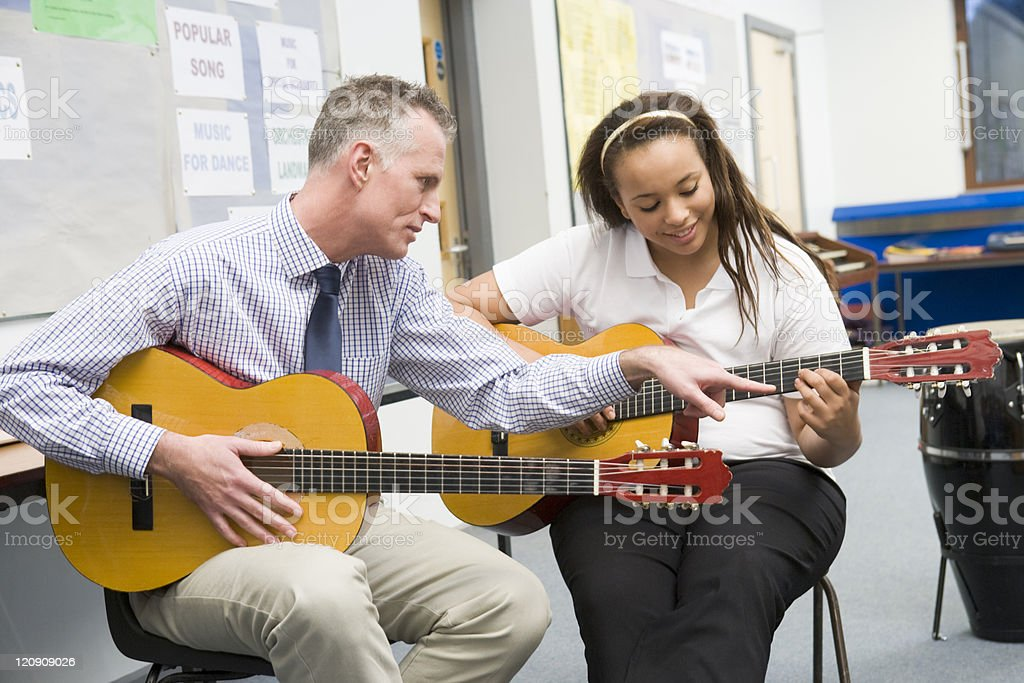 Schoolgirl and teacher playing guitar in music class stock photo