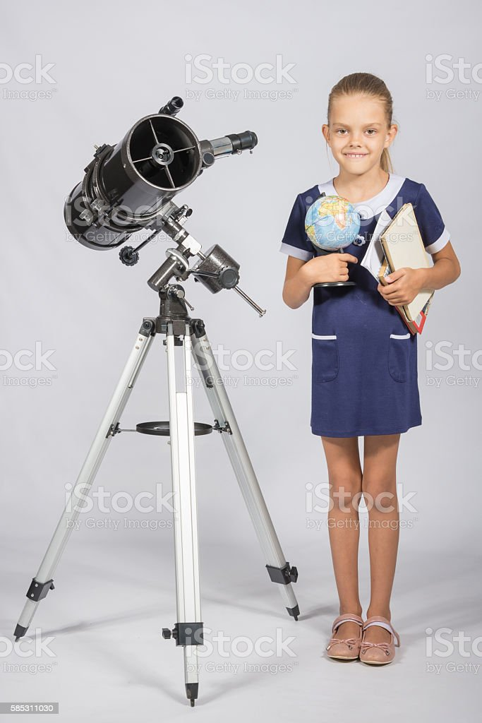 Schoolgirl astronomer is a telescope with a globe stock photo