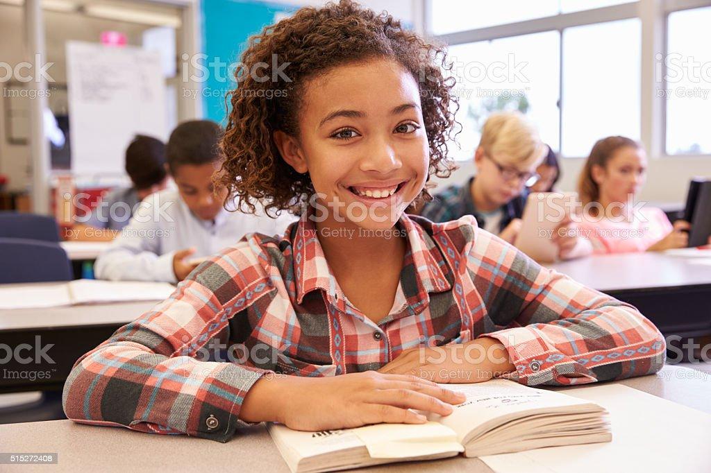 Schoolgirl at desk in elementary school looking to camera stock photo
