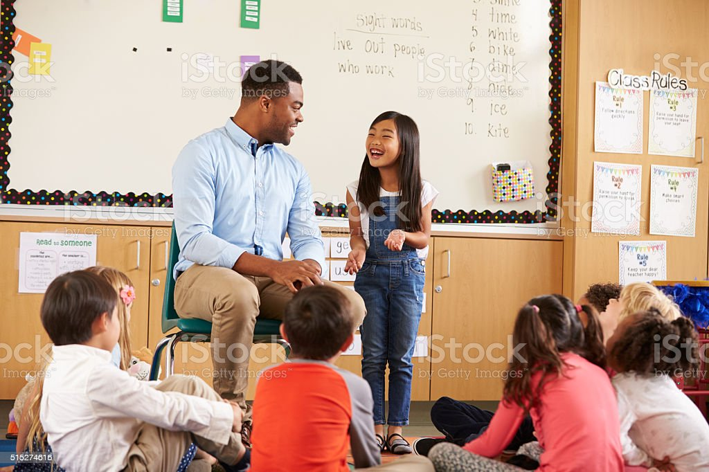 Schoolgirl at front of elementary class talking with teacher stock photo
