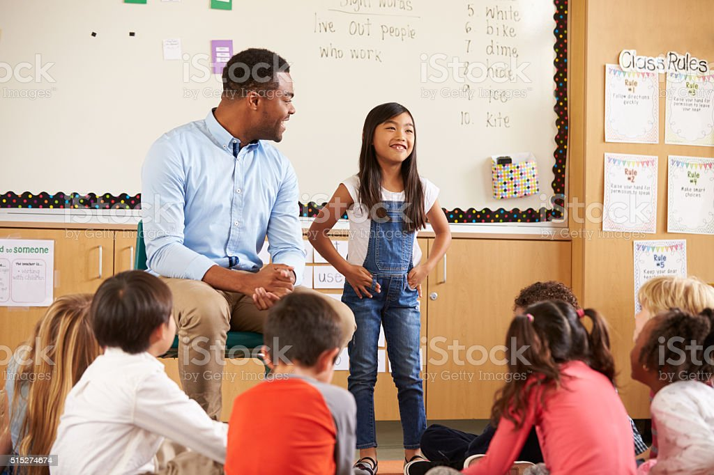 Schoolgirl at front of elementary class with teacher stock photo
