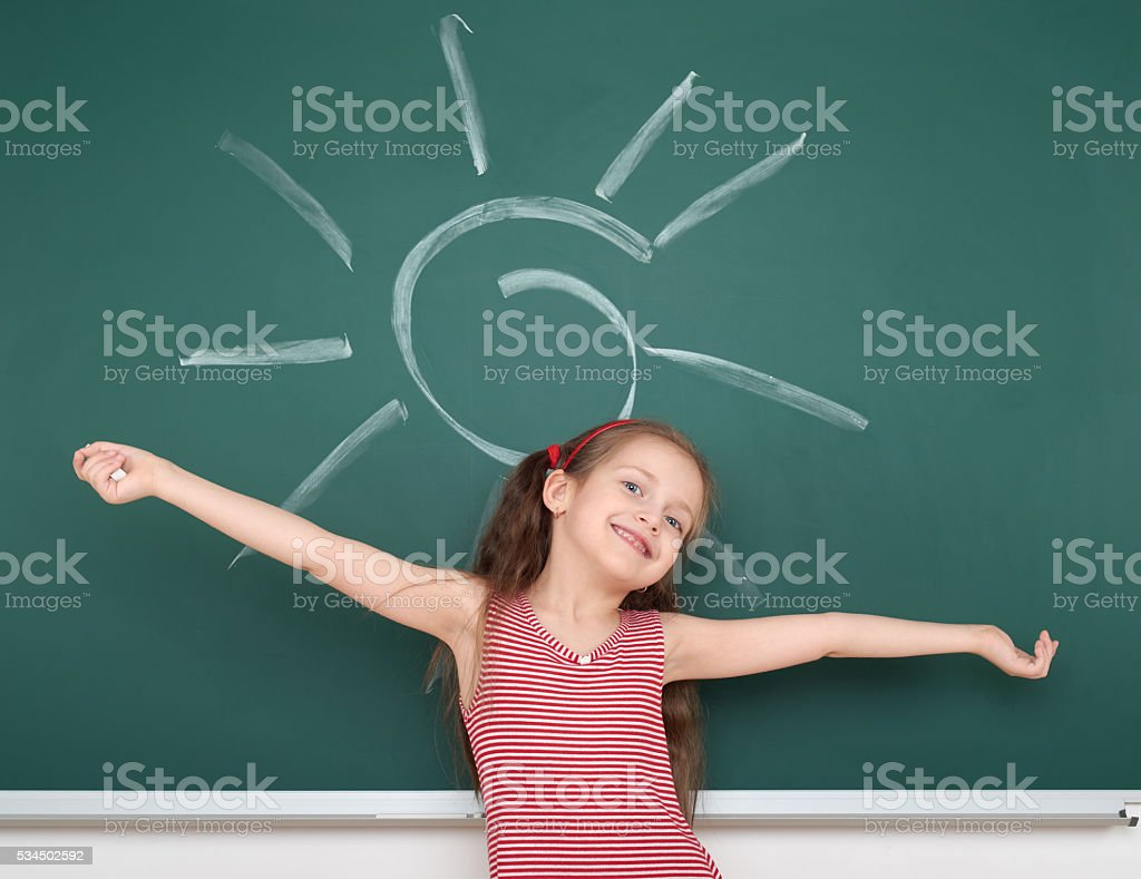 schoolgirl child drawing sun on green chalkboard stock photo